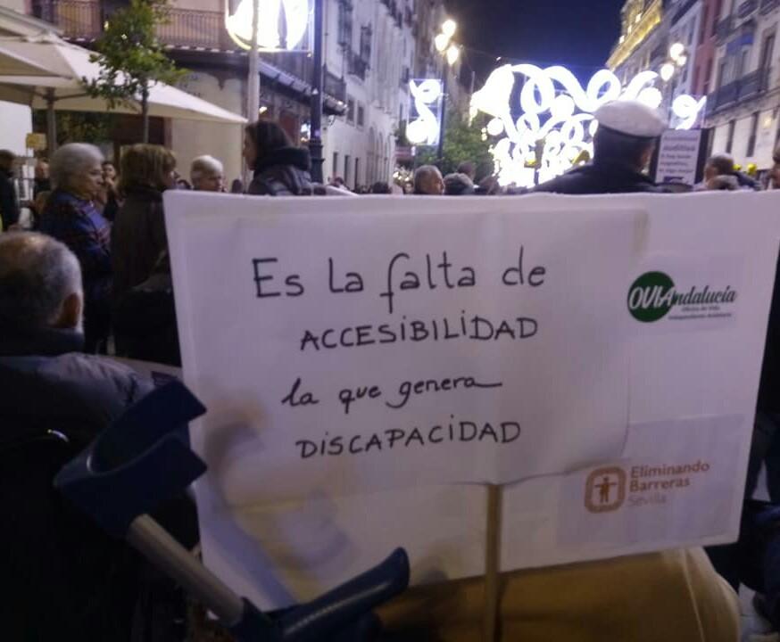 En una calle Sevillana los manifestantes portan una pancarta que dice: Es la falta de accesibilidad la que genera discapacidad
