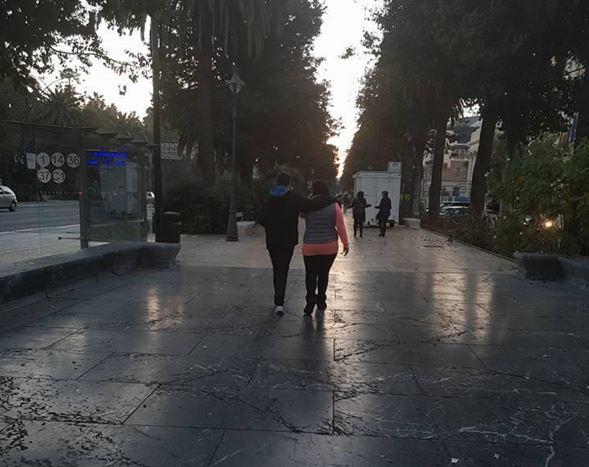 Dos personas paseando por el parque de espaldas a la cámara