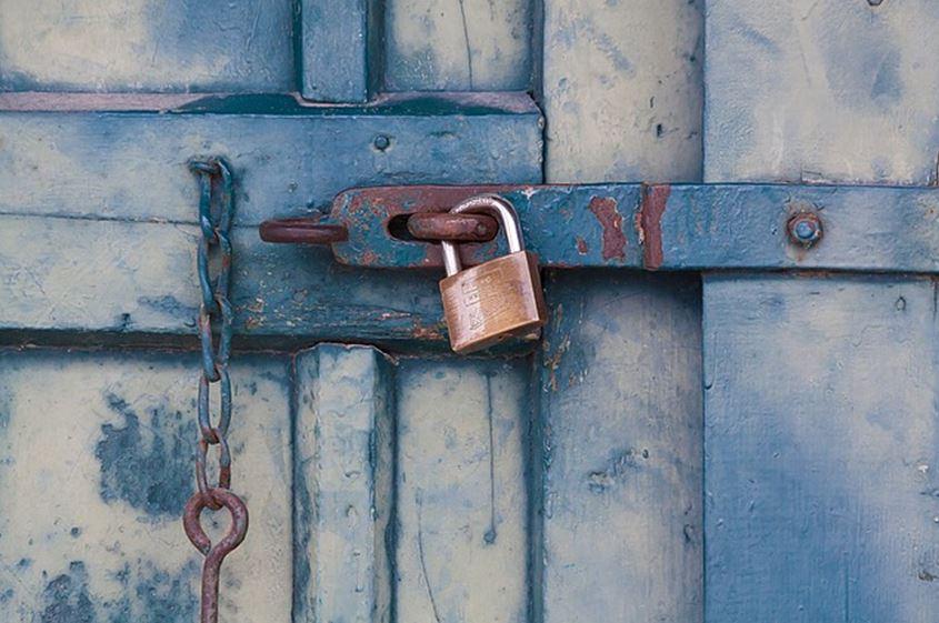Puerta de un establo cerrada con un candado