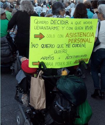 Persona en silla de ruedas con cartel reivindicando la Asistencia Personal.