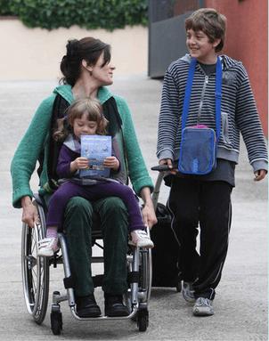 Mujer en silla con su hija pequeña en las piernas y charlando con el hijo mayor a la salida del colegio.