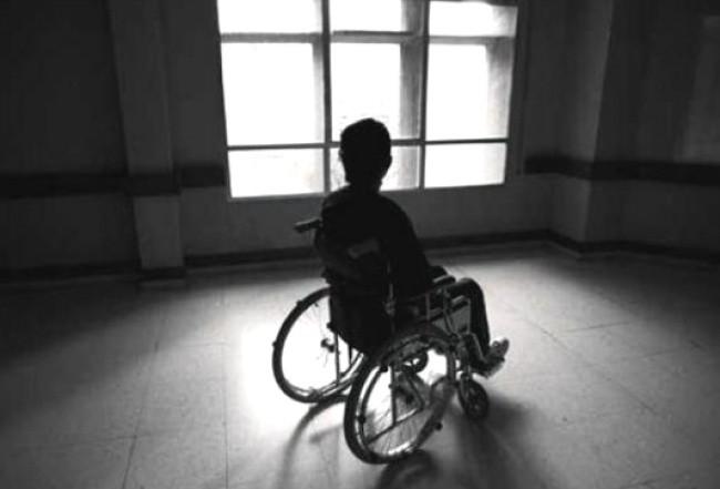 Imagen en blanco y negro de una mujer en silla de ruedas a contra luz en una habitación vacía